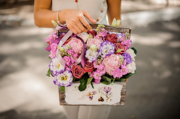 Женщина руки держит прекрасную композицию из цветов