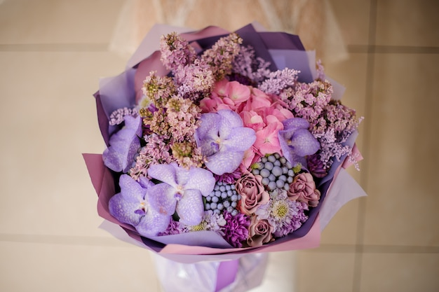 Девочка держит букет из нежной сирени и орхидеи, а также другие весенние цветы