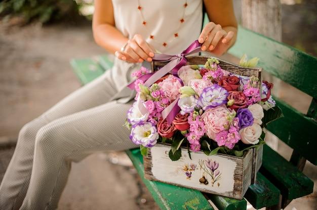 Женщина с прекрасной композицией из цветов