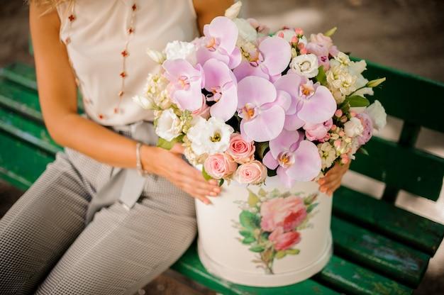 Женщина с прекрасной композицией красивых цветов