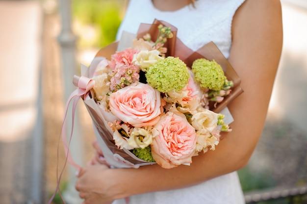 手で色とりどりの花の繊細なウェディングブーケ