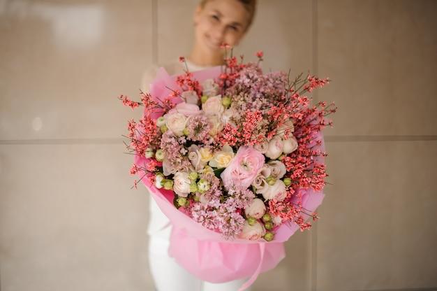 Улыбающаяся девушка держит весенний букет нежного розового цвета и белых цветов