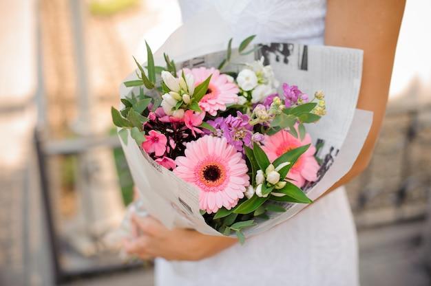 花のきれいな花束を保持している白いドレスを着た女性