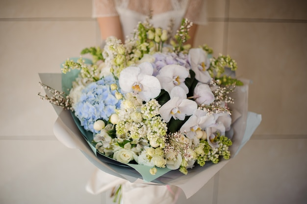 白いチューリップ、ライラック、蘭、アジサイの花束を持って女の子