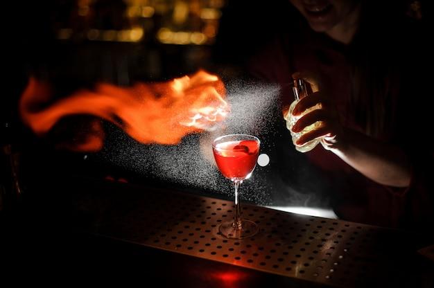 アペロールシリンジカクテルで満たされたカクテルグラスにピートウイスキーを振りかけ、スモーキーなメモを作る女性バーテンダー