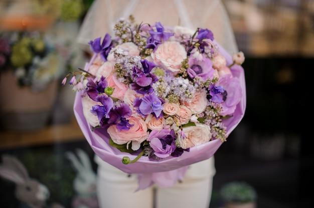 紫と柔らかいバラ色の花の花束を保持している女の子
