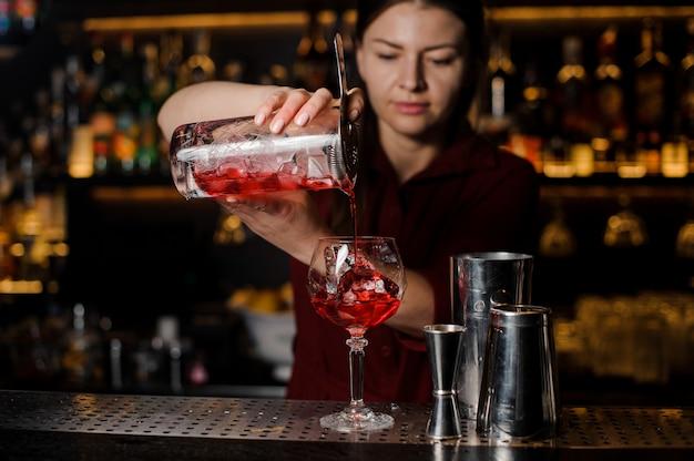 グラスに甘い赤いアルコール飲料を注ぐ美しい女性バーテンダー