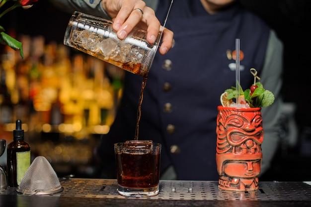 新鮮で冷たいアルコールカクテルをグラスに注ぐバーテンダー