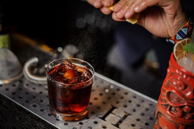 オレンジジュースをカクテルグラスに吹きかけるバーテンダーの手