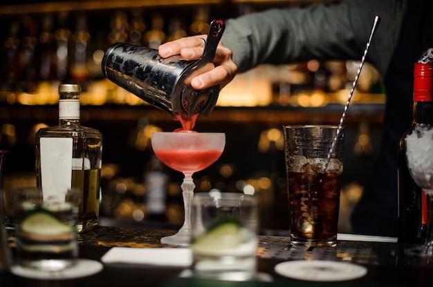 Бармен наливает в бокал свежий алкогольный коктейль