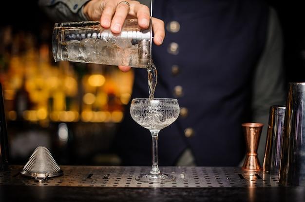準備ができたアルコールカクテルをグラスに注ぐバーマン