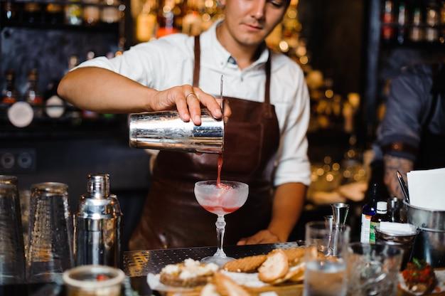 Бармен в коричневом кожаном фартуке наливает фруктовый алкогольный коктейль в бокал