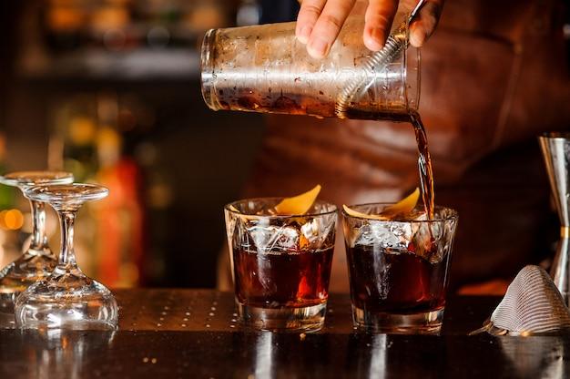 Бармен наливает алкогольный напиток в бокалы