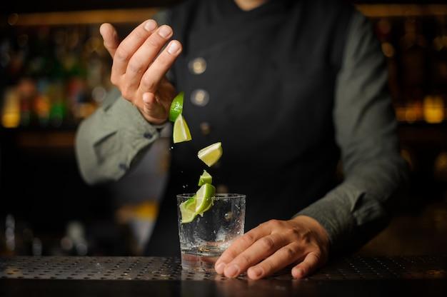 Бармен добавляет ломтики лайма в стакан