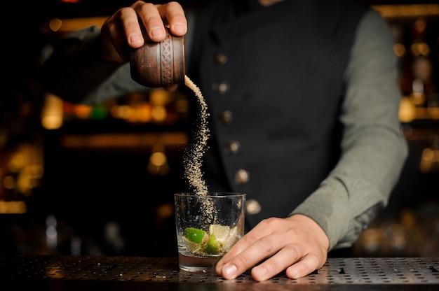 Бармен добавляя тростниковый сахар в бокал для коктейля с лаймом. процесс приготовления коктейля кайпиринья