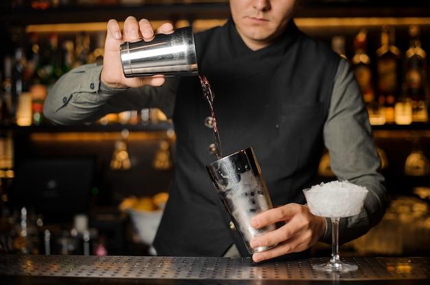 カクテルを作るための飲み物を混合するバーテンダー