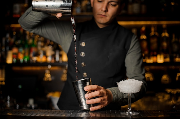 カンパリでカクテルを作るための飲み物を混合するバーマン