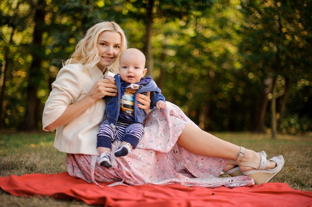 ピクニックに赤ちゃんの息子と素敵な母