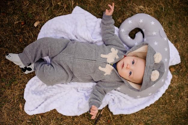 Милый малыш в комбинезоне с капюшоном лежит на подушке