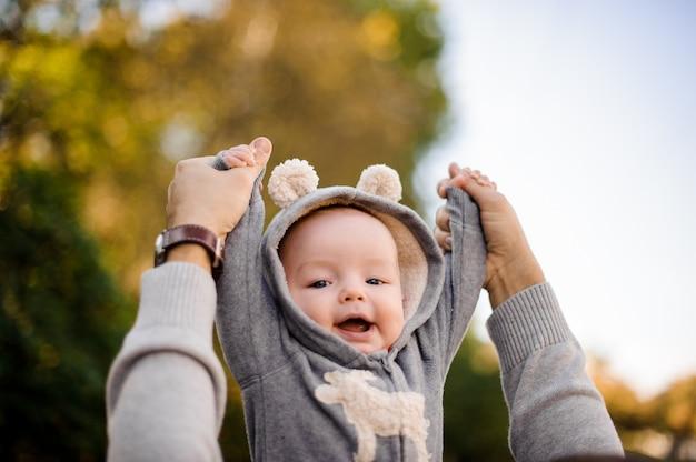 公園でかわいい笑顔の幼い息子を上げる父の手