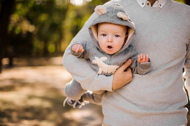 Отец держит милого маленького сына под мышкой