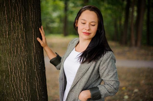 木の近くに立っている美しいブルネットの女性