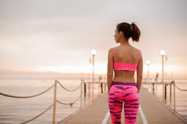 Вид сзади стройной и красивой женщины, одетой в розовую спортивную одежду на мостике