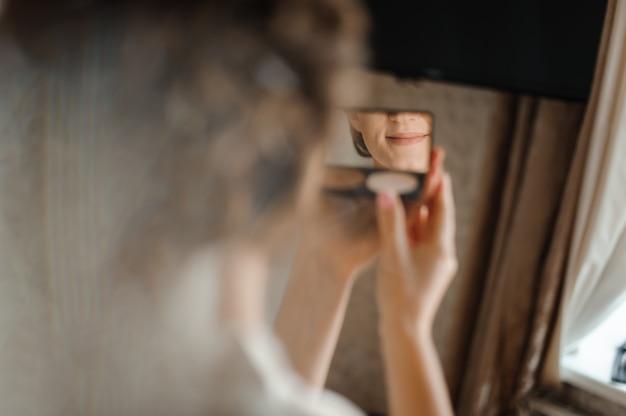 花嫁の朝の準備。鏡を見て美しい花嫁