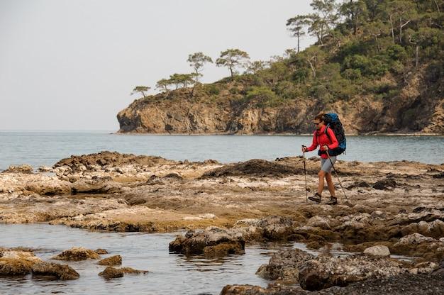 バックパックをハイキングで海の岩の上を歩く女の子