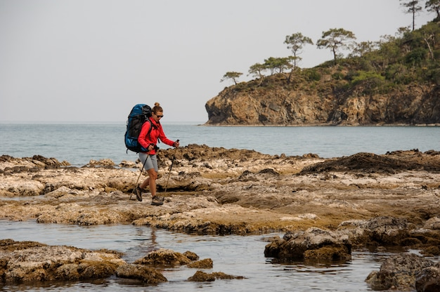 バックパックをハイキングで海の岩の上を歩く女性