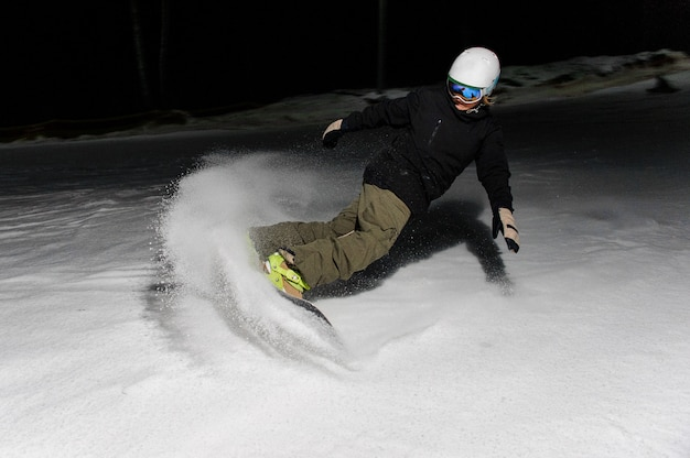 夜に山の斜面を下って乗って男性スノーボーダー