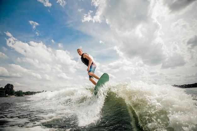 背の高い男が空を背景に川を下ってボードでウェイクサーフィン