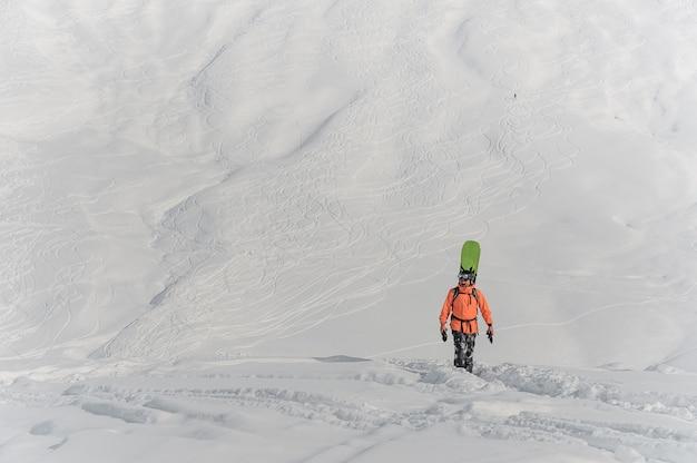 彼の背中の後ろにボードを持って歩くスノーボーダー