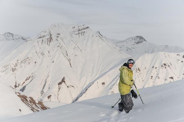 山のピークに笑みを浮かべて男性スノーボーダー