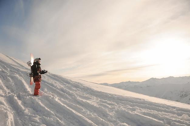 山の雪の上に立っている若いスノーボーダー