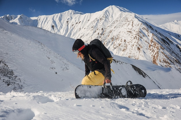 山でボードを持ってフリーライドスノーボーダー