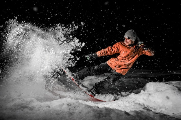 夜に雪の中でジャンプ若いフリーライドスノーボーダー