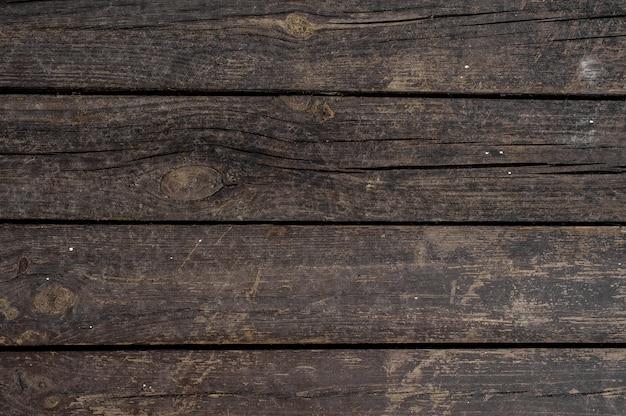 Закройте текстуру фона старых темных деревянных досок, горизонтально расположенных в стене