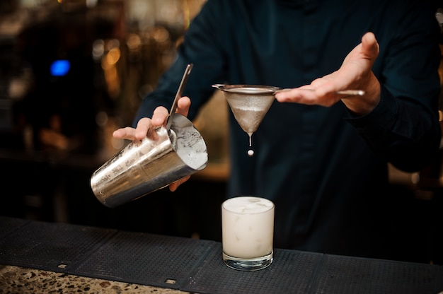 Бармен наливает молочный коктейль в бокал для коктейля