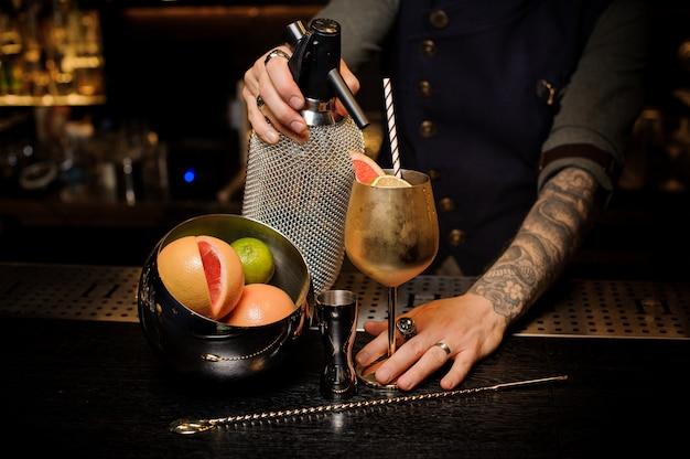 銅のカクテルグラスにソーダを注ぐタトゥーのバーマン
