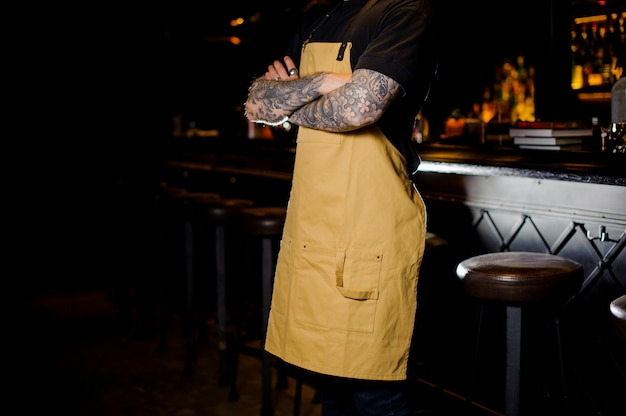 黄色のエプロンに身を包んだ手にタトゥーを持つバーテンダー