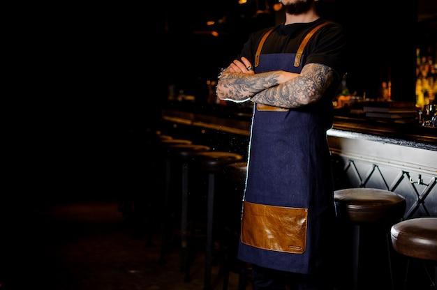 青と茶色のエプロンに身を包んだ手にタトゥーを持つバーテンダー