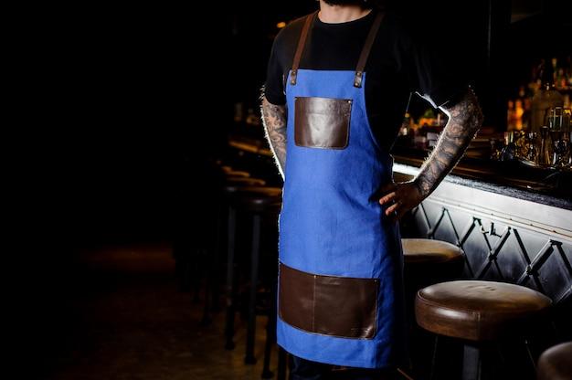 青と茶色のエプロンに身を包んだ手にタトゥーを持つ若いバーテンダー