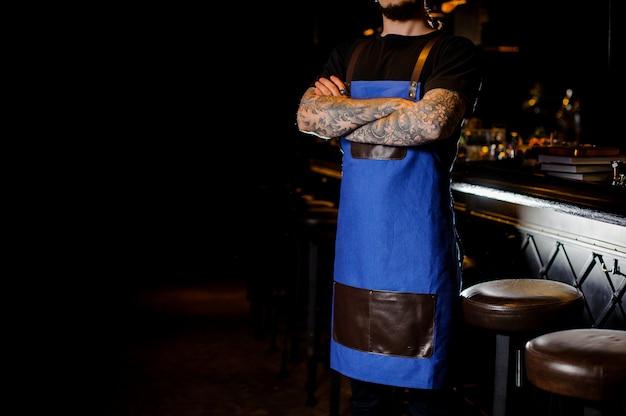 夜のクラブで交差させた手で青と茶色のエプロンに身を包んだ手にタトゥーを持つバーテンダー