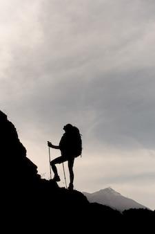 バックパックをハイキングし、杖で岩の上に立っている暗いシルエットガール