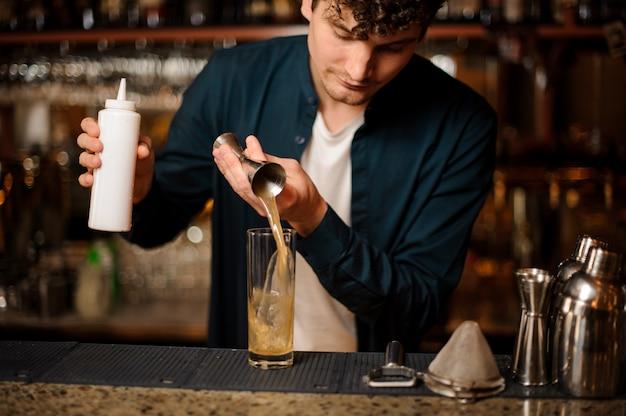 Молодой бармен наливает в стакан сладкий сироп
