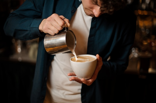 Молодой бариста наливает молоко в кофейную чашку