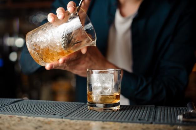 Бармен наливает свежий летний алкогольный коктейль в бокал