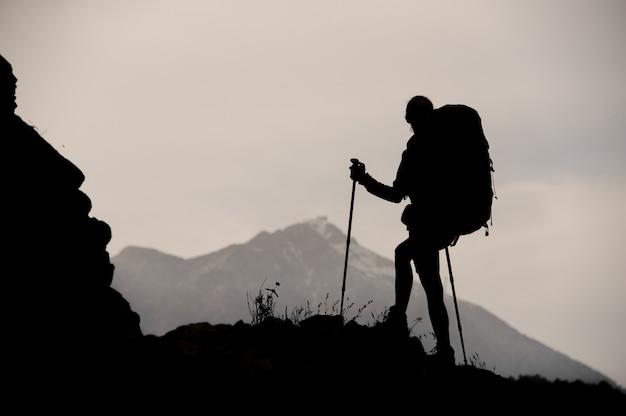 バックパックをハイキングし、杖で岩の上に立っているシルエットガール