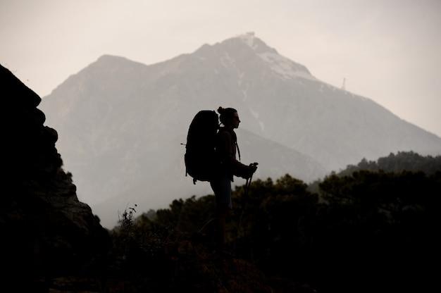 バックパックとスティックをハイキングで岩の上を歩くシルエットガール